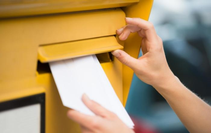 pagero - woman s hands inserting letter in mailbox 700x441 - Pagero